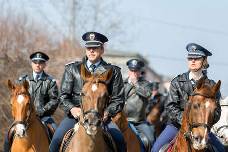 Sofia, Bulgaria - March 19, 2016: Policemen and policewomen from Horse police unit are riding the animals while participating in a parade at Saint Theodore's day.