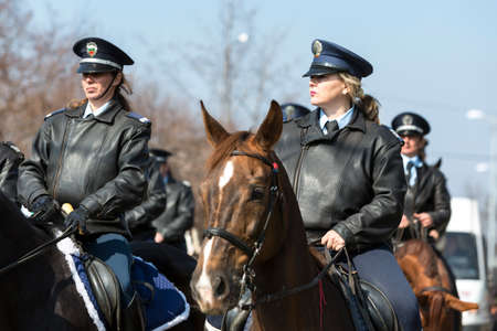 policewomen: Sofia, Bulgaria - March 19, 2016: Policemen and policewomen from Horse police unit are riding the animals while participating in a parade at Saint Theodores day. Editorial