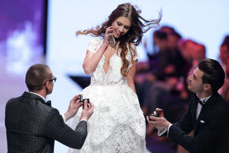 snows: Sofia, Bulgaria - March 23, 2016: Two male models are proposing a marriage at the runway to a female model at Sofia Fashion Week runway show. The fashion show is held for a second time in Bulgarias capital. Editorial