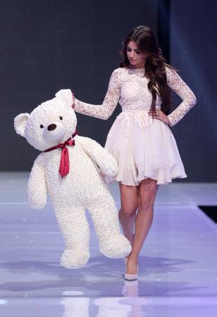 supermodel: Sofia, Bulgaria - March 23, 2016: A female model walks the runway with big white Teddy bear during the 2016 Sofia Fashion Week Show in Sofia, Bulgaria.