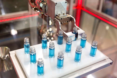 manipulating: Robotic mechanical arm is manipulating chemical tubes full with blue substance in a medical laboratory during a test. Stock Photo