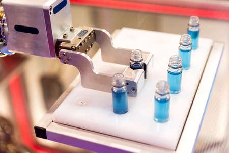 biotecnologia: brazo mec�nico robotizado est� manipulando tubos qu�micos completos con la sustancia azul en un laboratorio m�dico durante una prueba.
