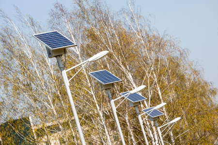 street lamps: Street lamps above an alley in the park. Every lamp with its own solar panel which collects the energy from the light for the evening. Stock Photo