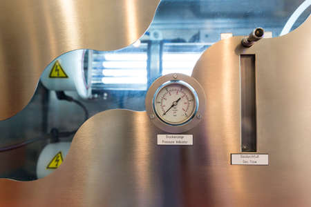refinement: Pressure indicator and gas flow indicator in an refinement machine system. Fluorescent lamps and high voltage labels inside. Water filtration system.