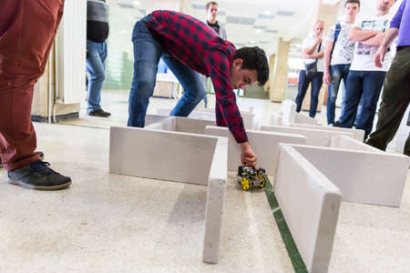 selfmade: Sofia, Bulgaria - April 5, 2016: A student is helping his self-made robot in a labyrinth during an open competition among school students.
