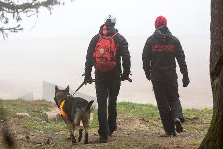 red cross: Sof�a, Bulgaria - 20 de abril 2016: Los hombres y sus perros en el equipo de b�squeda y rescate en la Cruz Roja de Bulgaria est�n participando en un entrenamiento en la monta�a de niebla.