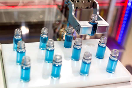 dozen: Blue liquid in a dozen of small laboratory test tubes during a medical science verification. A mechanical robotic arm taking one of the tubes. Stock Photo