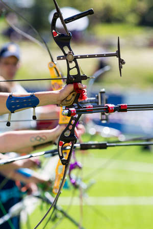 recurve: People are shooting with recurve bows during an archery competition. Hands and bows only.