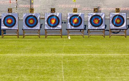 Six archery target rings during an archery competition. Green grass.