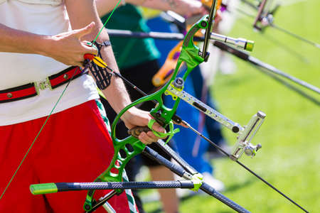 People are shooting with recurve bows during an archery competition. Hands and bows only. Green bow.