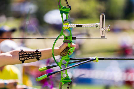 recurve: Person is shooting with recurve bow during an archery competition. Hand and bow only. Green bow.