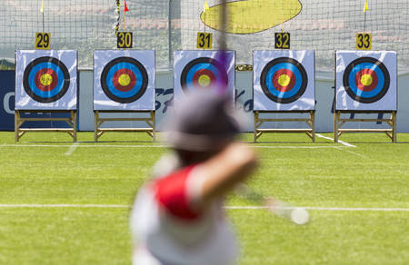 recurve: A person is shooting with recurve bow on a target during an archery competition. Focus on the targets. Stock Photo