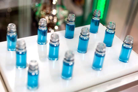 dozen: Blue liquid in a dozen of small laboratory test tubes during a medical science verification.