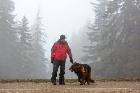 cruz roja: Sofía, Bulgaria - 20 de abril 2016: Un hombre y su perro en el equipo de búsqueda y rescate en la Cruz Roja de Bulgaria están participando en un entrenamiento en la montaña de niebla.