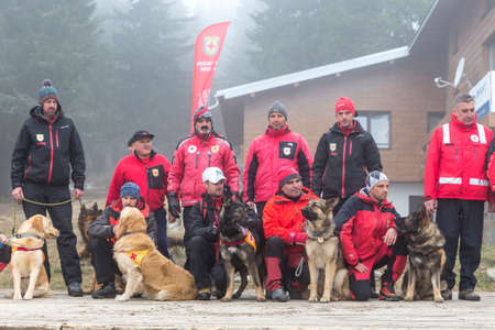red cross: Sofia, Bulgaria - April 20, 2016: Men and their dogs at the search and rescue team at Bulgarian Red Cross are posing for a group picture in the mountain.