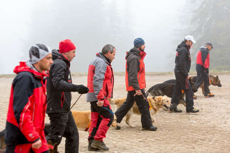 Sofia, Bulgaria - April 20, 2016: Men and their dogs at the search and rescue team at Bulgarian Red Cross are participating in a training in the foggy mountain.