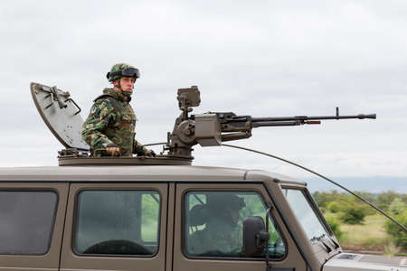 americal: Sofia, Bulgaria - May 4, 2016: Military vehicle with heavy machine gun and a soldier. Growler - an internally transportable light strike vehicle. Light utility, light strike and fast attack vehicle.
