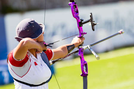 recurve: An young girl is shooting with a recurve bow during un open archery competition. Stock Photo
