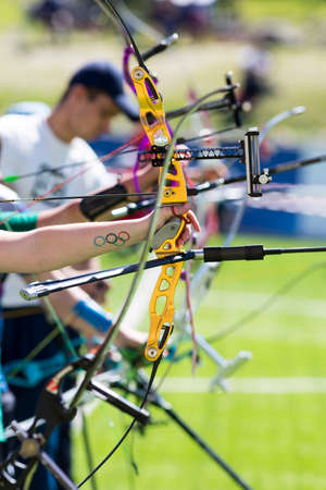recurve: People are shooting with recurve bows during un open archery competition. Bows nad hands only.