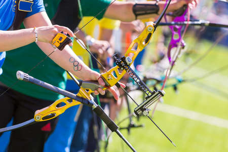 People are shooting with recurve bows during un open archery competition. Bows nad hands only. 免版税图像 - 56508225