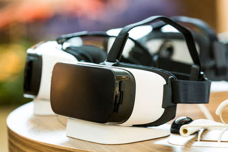 simulate: Virtual reality (VR) headsets (glasses) on a table. VR is immersive multimedia or computer-simulated reality - a computer technology that replicates an environment and simulates a users physical presence and environment to allow for user interaction