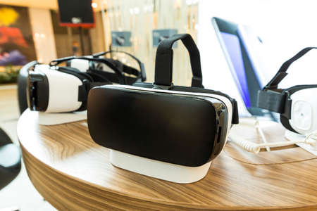 presence: Virtual reality (VR) headsets (glasses) on a table. VR is immersive multimedia or computer-simulated reality - a computer technology that replicates an environment and simulates a users physical presence and environment to allow for user interaction