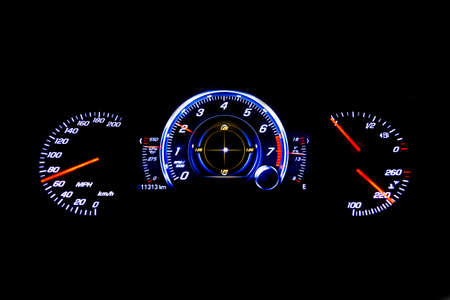mph: Dashboard and digital display of a modern car, mileage, fuel consumption, speedometer. New and colorful light indicators isolatred on a black background. Closeup. Miles per hour - MPH. Stock Photo