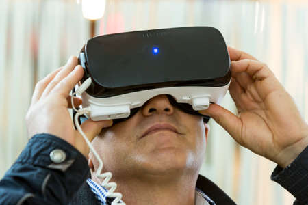 simulate: Sofia, Bulgaria - May 13, 2016: A man experiences virtual reality mounting a (VR) headsets (glasses) rig on his head during an exhibition for new technologies. Editorial