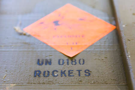 munition: Green ammunition boxes with rocket-propelled grenades (RPGs) in a munition producing factory. Highly dangerous explosives. Explosive sign. UN 0180 ROCKETS.