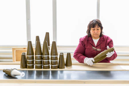 munition: Sopot, Bulgaria - May 17, 2016: Female worker is checking explosive element of anti tank rocket-propelled grenades (bazooka) at an assembly line in a munition factory. Working with white gloves.