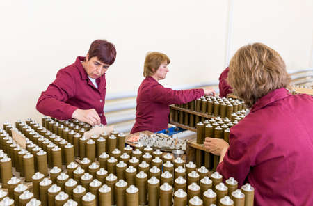 bazooka: Sopot, Bulgaria - May 17, 2016: Female workers are checking explosive elements of anti tank rocket-propelled grenades (RPG, bazooka) near the assembly line in a munition factory. Editorial