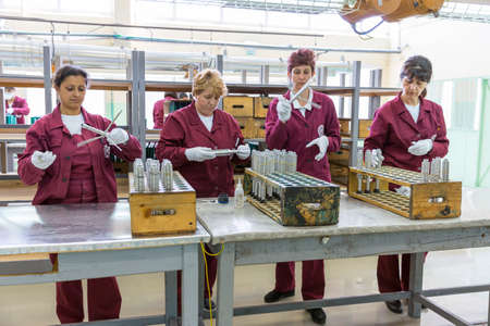 Sopot, Bulgaria - May 17, 2016: Workers are preparing explosive triggers of anti tank rocket-propelled grenades (RPG, bazooka) at an assembly line in a munition factory. Dangerous wotking conditions. Editoriali