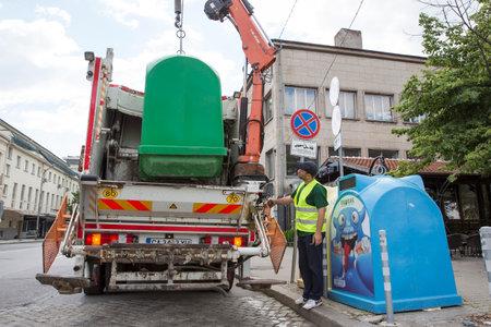 camion de basura: Sof�a, Bulgaria - 26 may, 2016: Un trabajador sanitario es recoger los contenedores de basura con su cami�n de reciclaje. Contenedores para recogida selectiva de residuos.