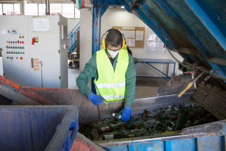 glass recycling: Sofia, Bulgaria - May 26, 2016: Glass waste worker is recycling glass bottles in a recycling facility. Different glass packaging bottle waste. Glass waste management. Editorial