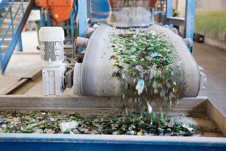 glass recycling: Glass particles for recycling in a machine in a recycling facility. Different glass packaging bottle waste. Stock Photo