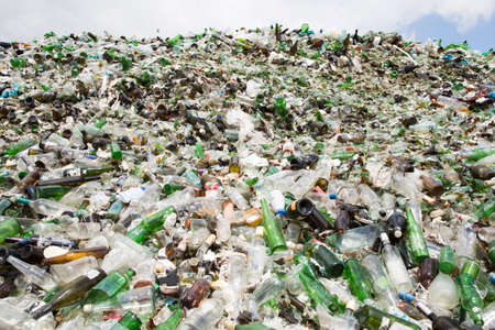 Glass waste for recycling in a recycling facility. Different glass packaging bottle waste. Glass waste management. 免版税图像