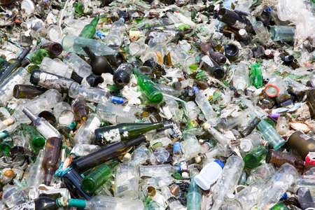 reprocessing: Glass waste for recycling in a recycling facility. Different glass packaging bottle waste. Glass waste management. Stock Photo