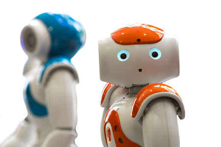 with orange and white body: Small robots with human face and body - humanoid. Artificial Intelligence - AI. Orange and blue robots isolated on white background.