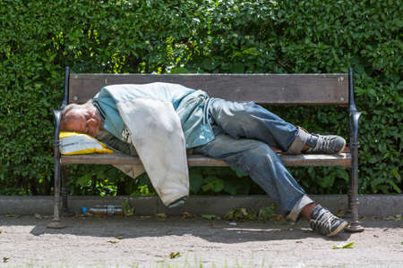 destitution: Sofia, Bulgaria - May 18, 2016: Homeless man during day sleeping on a bench in a park.