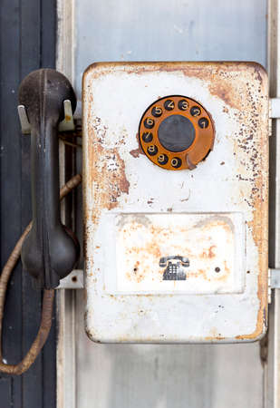 pay wall: Rusty old vintage rotary pay phone for public use. Old pay telephone with coin slots on a wall.