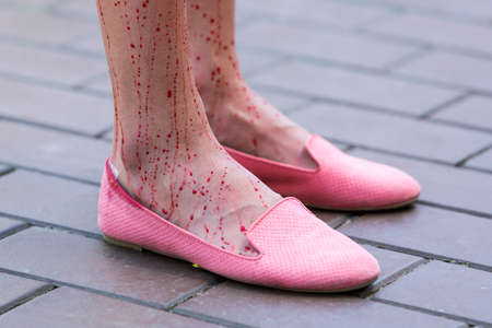 womans clothing: Vegans and vegetarians animal rights activists covered themselves in blood and wrapped themselves in meat packaging protesting against killing animals for meat or clothing. Womans bloody legs and feet. Pink shoes.