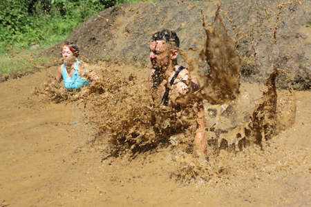 Sofia, Bulgaria - July 9, 2016: Participants are jumping into muddy water at the Legion Run extreme sport challenge near Sofia. The sports event is mud and obstacle course designed to test peoples physical strength, stamina, and mental grit.