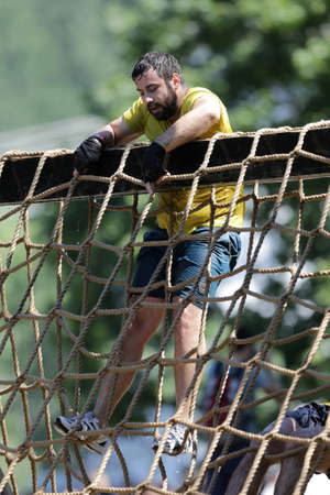 grit: Sofia, Bulgaria - July 9, 2016: A participant is climbing at the Legion Run extreme sport challenge near Sofia. The sports event is mud and obstacle course designed to test peoples physical strength, stamina, and mental grit.
