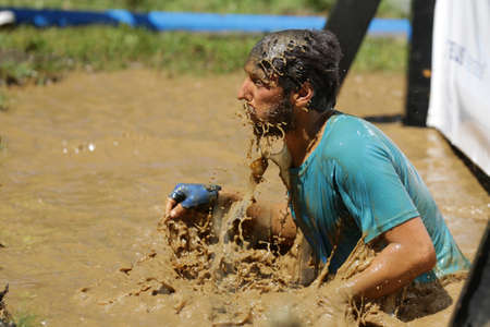 Sofia, Bulgaria - July 9, 2016: A participant is jumping into muddy water at the Legion Run extreme sport challenge near Sofia. The sports event is mud and obstacle course designed to test peoples physical strength, stamina, and mental grit.