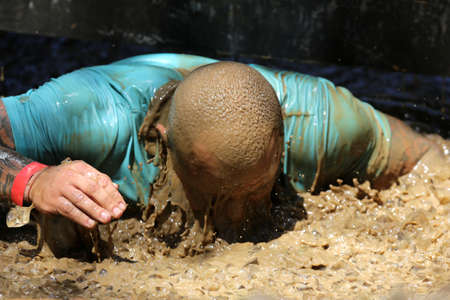 legion: Sofia, Bulgaria - July 9, 2016: A participant is diving in an iced water at the Legion Run extreme sport challenge near Sofia. The sports event is mud and obstacle course designed to test peoples physical strength, stamina, and mental grit. Editorial