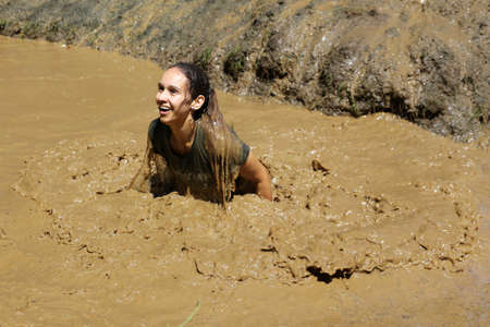 Sofia, Bulgaria - July 9, 2016: A participant is jumping into muddy water at the Legion Run extreme sport challenge near Sofia. The sports event is mud and obstacle course designed to test people's physical strength, stamina, and mental grit.