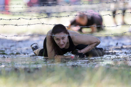 Sofia, Bulgaria - July 9, 2016: A participant is crawling through water under electrified wires at the Legion Run extreme sport challenge near Sofia. The sports event is mud and obstacle course designed to test people's physical strength, stamina, and men