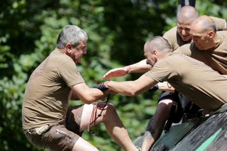 grit: Sofia, Bulgaria - July 9, 2016: Participants are participating at the Legion Run extreme sport challenge near Sofia. The sports event is mud and obstacle course designed to test peoples physical strength, stamina, and mental grit.