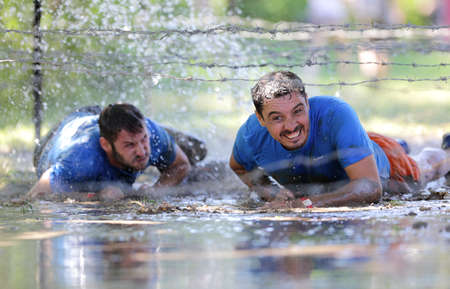 Sofia, Bulgaria - July 9, 2016: Participants are crawling through water under electrified wires at the Legion Run extreme sport challenge near Sofia. The sports event is mud and obstacle course designed to test peoples physical strength, stamina, and men