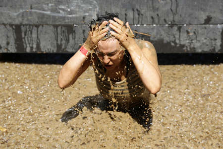 grit: Sofia, Bulgaria - July 9, 2016: A participant is diving in an iced water at the Legion Run extreme sport challenge near Sofia. The sports event is mud and obstacle course designed to test peoples physical strength, stamina, and mental grit. Editorial